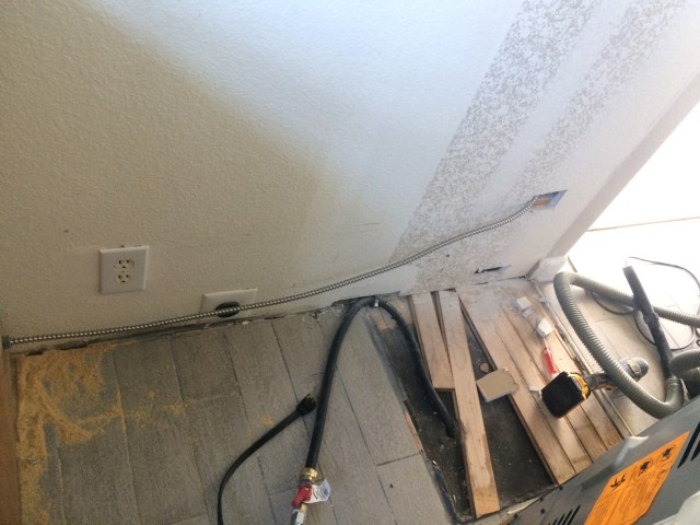 Metal cable run behind stove