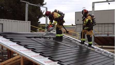Firefighters destroy a Tesla roof