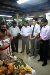 A Hindu priest blesses the inauguration of the new sachet-making machine at a factory in Sri Lanka.