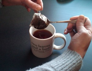Using the sachet's string and a spoon to squeeze the heck out of a tea sachet.
