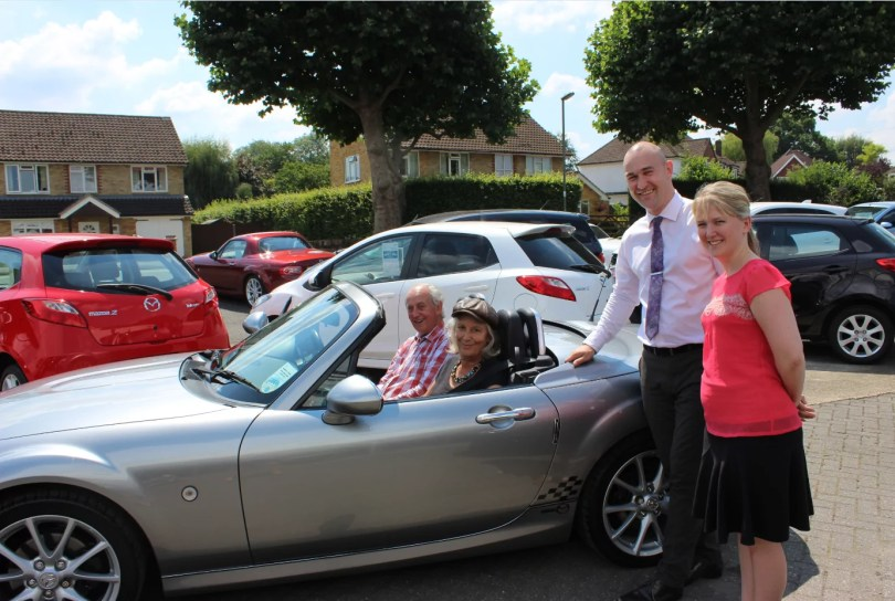 Adrian Arnold, Sales Executive and Amy Paterson, Marketing Manager, wave off Mr and Mrs Wetton in their new MX-5