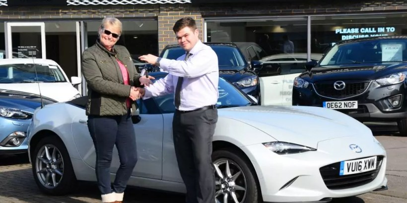 T W White & Sons handing over the keys to a brand new Mazda MX-5 in white