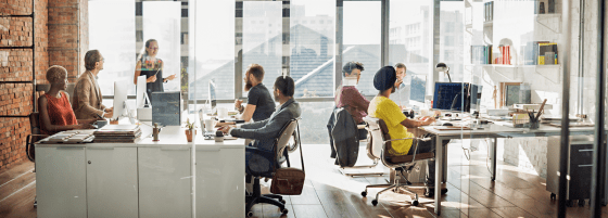 office workplace with 8 employees at desks or talking