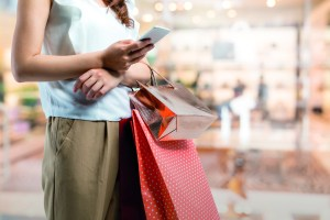 Shopping Concept. Woman Using Smart Phone With Shopping Bag.