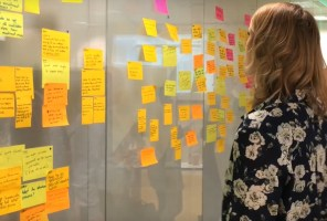 Woman looking at post-it notes capturing brainstorming