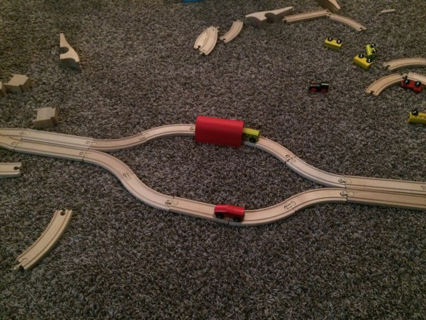 A set of wooden IKEA trains is being played with on brown carpeting. Two symmetric paths after a split are set up, one train on each, one path obscured by a red plastic tunnel, mimicking certain laser experiments.