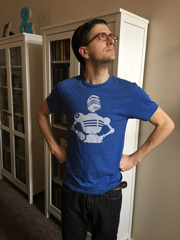 Nick stands in a superhero pose wearing a blue tee shirt depicting a robot with a microphone head in a superhero pose, the logo of The Incomparable podcast network.