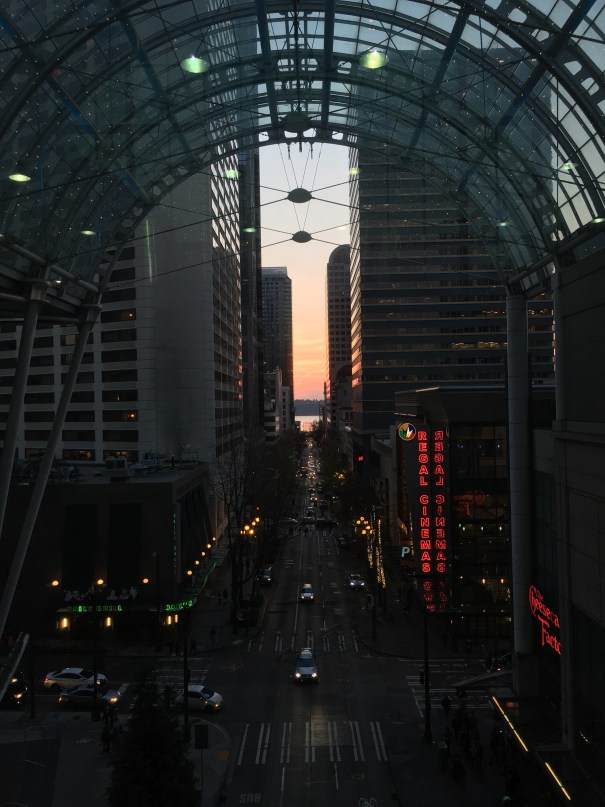 The white awning of the WSCC skybridge is in the foreground of this shot down Pike St to the SW with the Pike Place Market sign at the end and a red sky behind the Olympics across the bay.