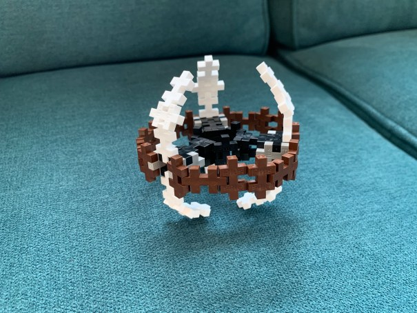 A vaguely DS9 shaped model in black, brown, and white on a teal couch