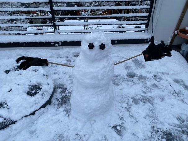 Rooftop snow person built with three balls, bamboo stakes, and work gloves.