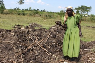 Karen, grandmother and guardian to two CFCA sponsored children in Kenya, shows the rubble of her home after it was destroyed by a flood.
