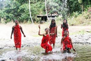 Mylene, center, splashes in the water with other Dumagat young people.