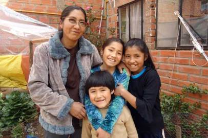 Bolivian mom Florencia and her three oldest kids in their urban garden.