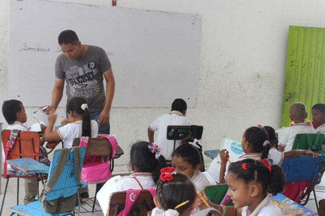 John teaches students in his classroom.