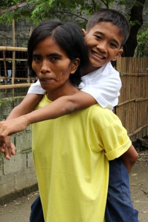 Virgilio's mother carries him on her back to school.