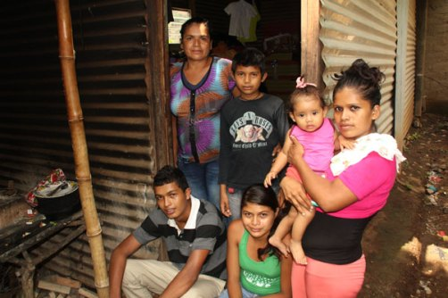 Morena stands in the doorway of her home with her family.