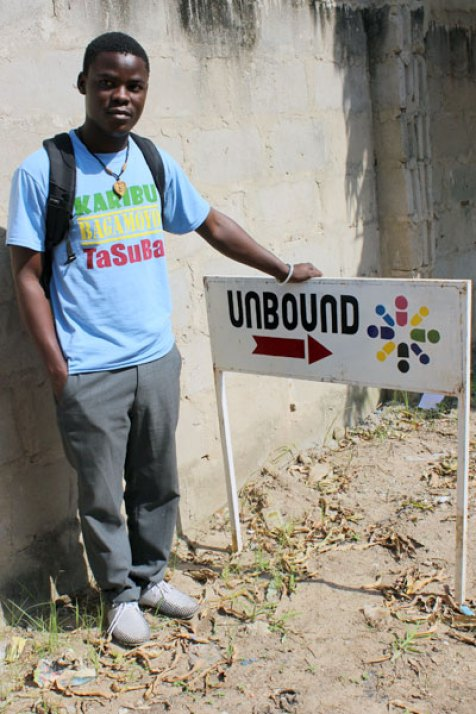Shija stands next to the sign he painted for Unbound's coordinating office in Tanzania.