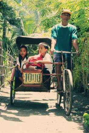 Sponsored children Riza Mae (left), Kempee (partially visible in back), and John (holding a red bag) are transported to school in a pedicab driven by Kempee's father, Johnny. The children live in Tabaco City in the eastern Albay province of the Philippines.