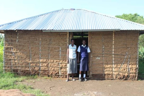 A mother and daughter in Kenya stand in front of their newly built home.