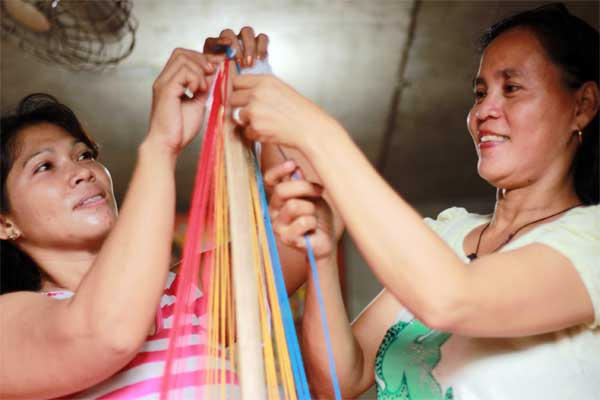 Mila (left) and Louella (right), whose children are sponsored through Unbound, use yarn tied to a stick at the top and in a circle at the bottom to create the conical shape of a Christmas tree.