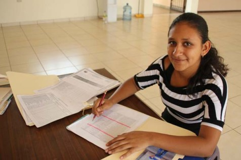 A young woman in El Salvador works on homework.