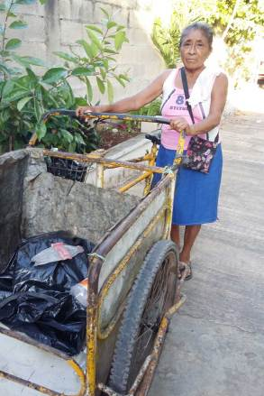 Eustaquia puts items that can be recycled into her cart.