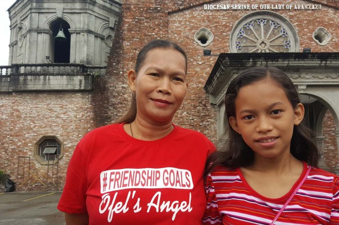 A mother and daughter in front of a Catholic church in the Philippines.