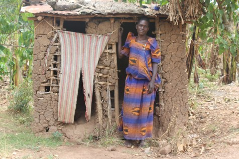 Image = Nakitende stands in the doorway of her family's old latrine.