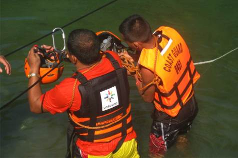 An image of a member of the Philippine coast guard teaching another man about water safety.
