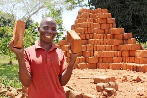 Photo of a man in Uganda displaying freshly dried bricks he's made.