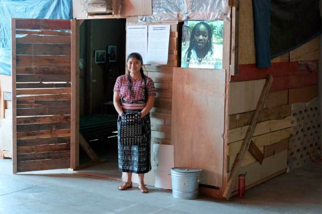 An image of a young woman standing outside a model home typical of the homes found in empoverished areas.