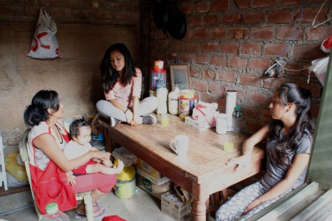 An image of Sonia and her daughters at their kitchen table.