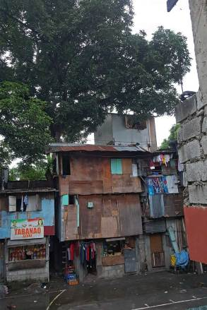 The gray fourth-floor annex apartment near the treetop belongs to An-An and her family. It was tacked on to the existing structure when they moved to the Calvary Hill neighborhood.
