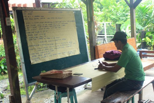 A member of the ERPAT fathers group reviews information about local conditions following Typhoon Henry.