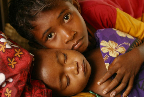 Papua Nya Guinea: Katuwala, 10 år, omfamnar sin sovande lillebror Kalu. Tio månader gamla Kalu lider av malaria, en vanlig orsak till dödsfall bland barn i landet. Foto: Giacomo Pirozzi
