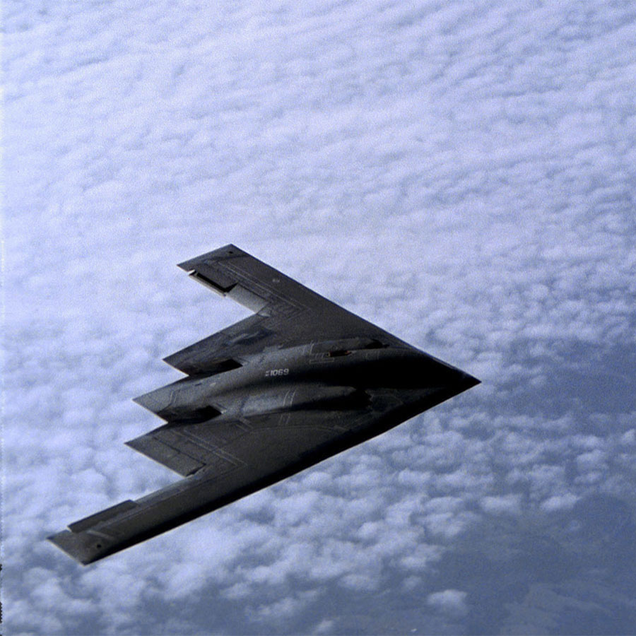 A B-2 Spirit bomber flies across an open stretch of sky. The B-2 Spirit is a multi-role bomber capable of delivering both conventional and nuclear munitions.