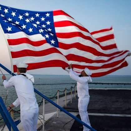 Sailors assigned to the color guard aboard the aircraft carrier USS Dwight D. Eisenhower (CVN 69) retire the colors. Dwight D. Eisenhower is pierside during the sustainment phase of the Optimized Fleet Response Plan (OFRP).