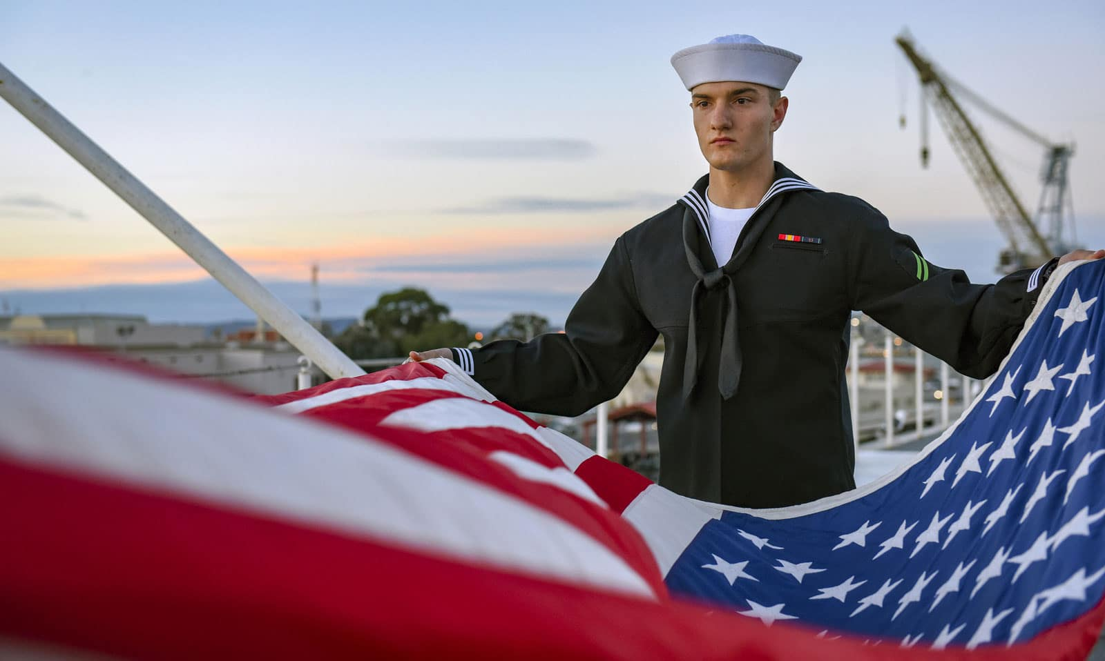 U.S. Navy Airman Apprentice Andrew Mackey performs evening colors aboard the aircraft carrier USS Carl Vinson (CVN 70). The Vinson Carrier Strike Group (CSG) is preparing to depart on a regularly-scheduled deployment to the Western Pacific where it will conduct bilateral exercises in the Indo-Asia-Pacific region.
