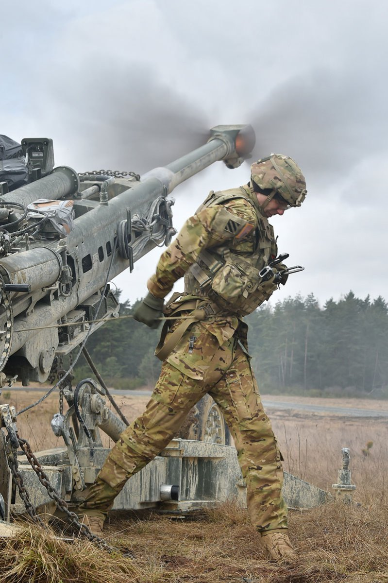 U.S. Army Spc. Vincent Ventarola Pulls the Lanyard on a M777 Howitzer
