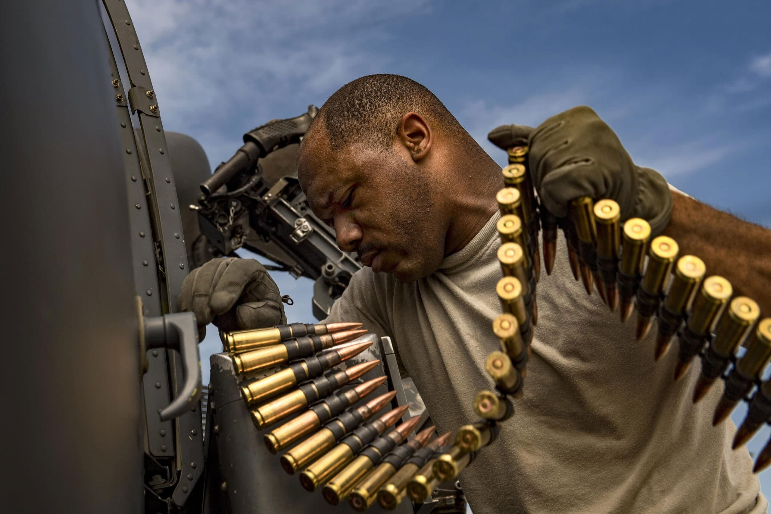 United States Air Force Tech. Sgt. Brandon Middleton loads a can of whoop-ass .50-caliber rounds into a machine gun on an HH-60G Pave Hawk helicopter at Moody Air Force Base, Georgia.