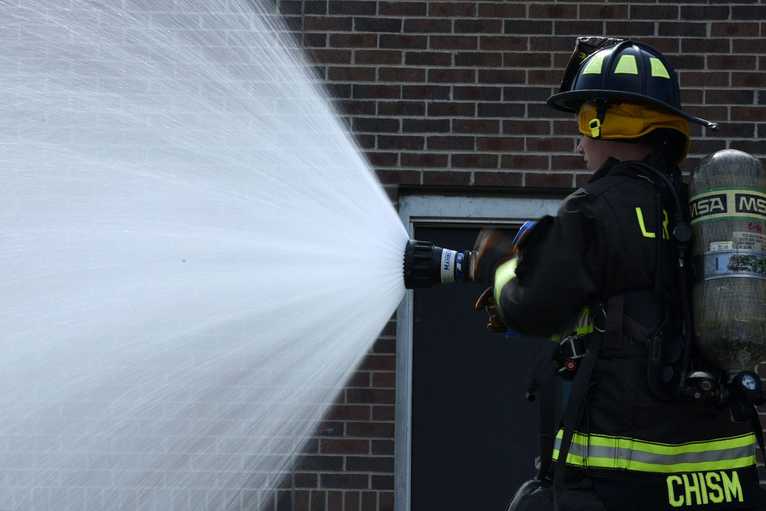 U.S. Air Force Airman Shyanne Chism firefighter apprentice, inspects a fire hose. Little Rock AFB firefighters train regularly to ensure they are prepared to respond to any emergency.