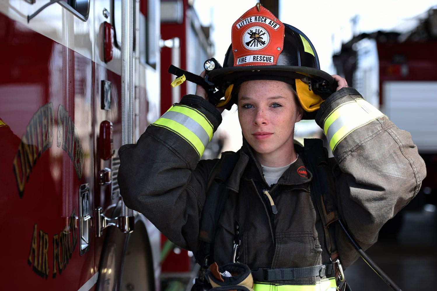 U.S. Air Force Airman Shyanne Chism, 19th Civil Engineer Squadron Fire Department firefighter apprentice, dons her helmet at Little Rock Air Force Base, Ark. Firefighters traditionally fold their gear before formal roll-calls, which announce the official change of individuals on shift and allows firefighters to brief each other on any happenings.