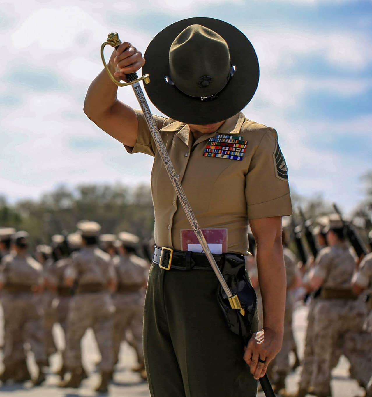 USMC Senior Drill Instructor Gunnery Sgt. Mayra Garcia returning her sword to her scabbard during a final drill evaluation at Peatross parade deck.