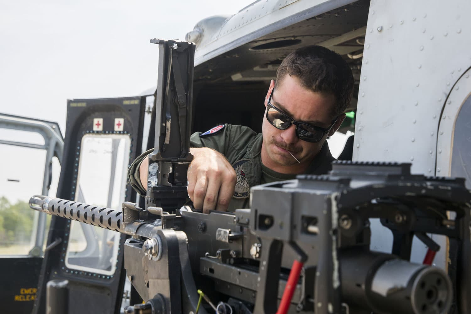 U.S. Marine Corps Cpl. Matthew T. Glora, a UH-1Y Huey crew chief with Marine Light Attack Helicopter Squadron 269, inspects a GAU-21 .50 caliber machine gun during Northern Strike at the Combat Readiness Training Center Alpena, MI.