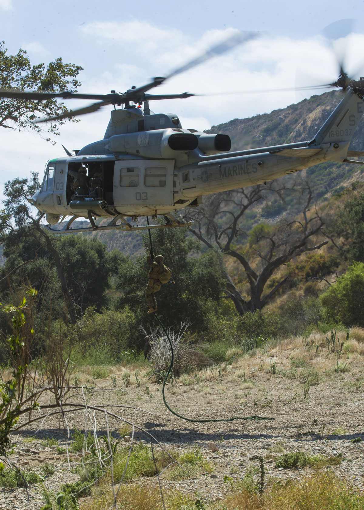 Marines with 1st Air Naval Gunfire Liaison Company (ANGLICO) rappel from a Bell UH-1 Iroquois on Camp Pendleton.