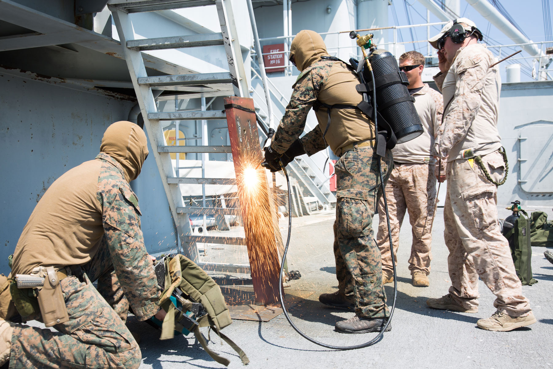 US Marines with the Maritime Raid Force (MRF) utilize a torch to practice thermal breaching techniques.