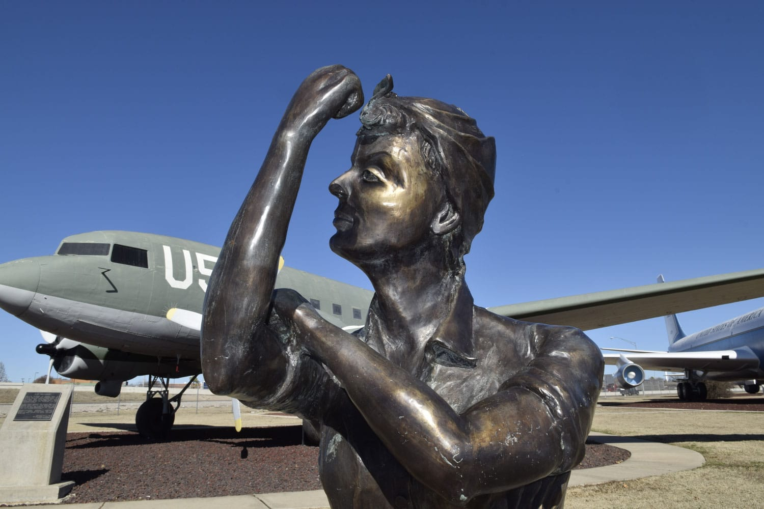Many women worked in the Douglas Aircraft manufacturing plant in Oklahoma City to produce C-47 aircraft like the one visible behind her. The free public park features aircraft operated or maintained by Tinker AFB over the years and is located near the main entrance to the base with free parking available.