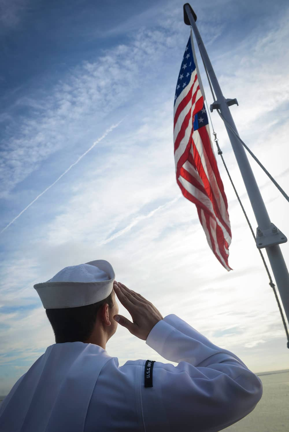 United States Navy Yeoman 3rd Class Zachary Tulley salutes the American flag on the fantail of the amphibious assault ship USS Iwo Jima during morning colors. Iwo Jima is conducting a scheduled continuous maintenance availability in preparation for their upcoming deployment.