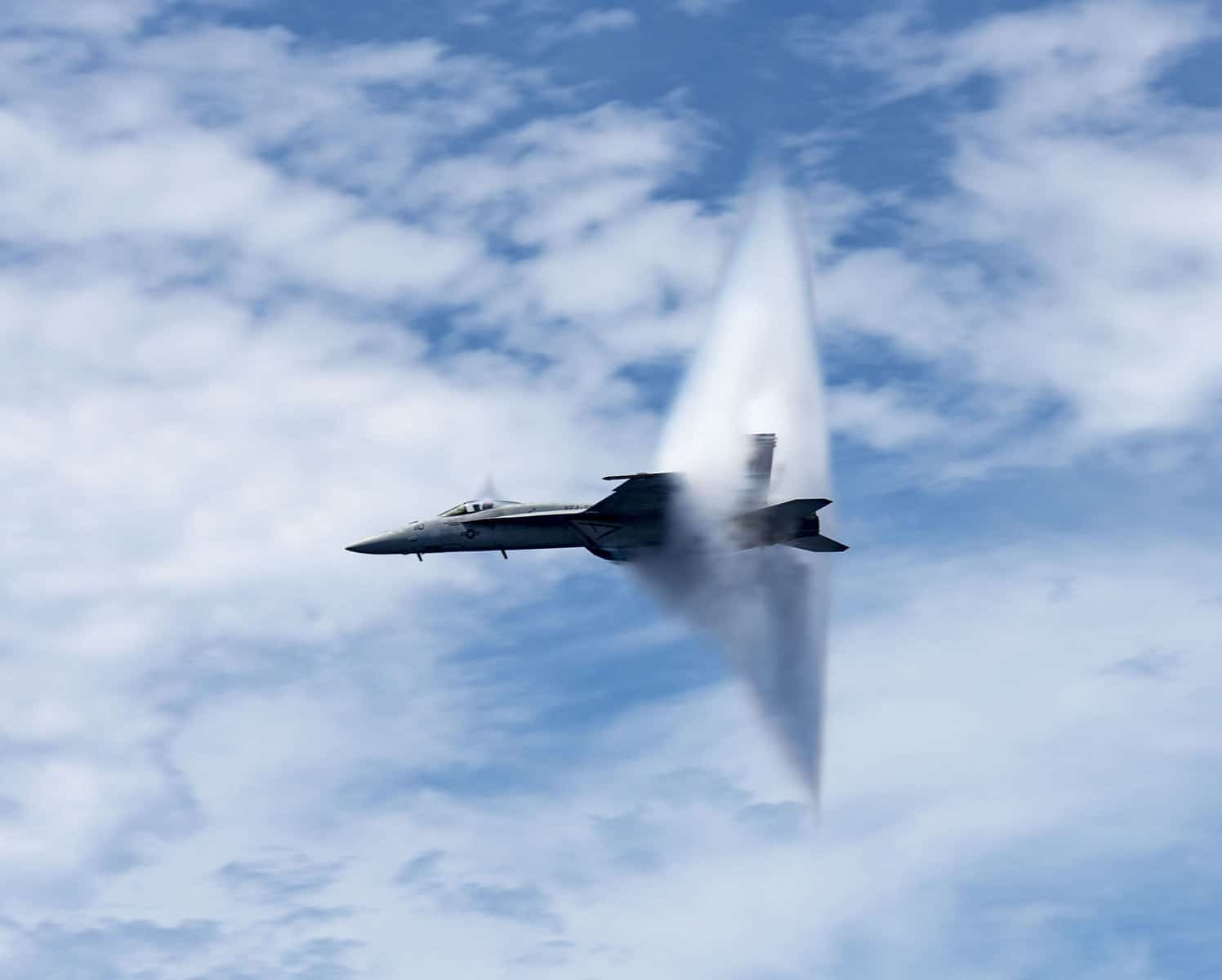 "A United States Navy F/A-18E Super Hornet assigned to the ""Tomcatters"" of Strike Fighter Squadron 31 breaks the sound barrier above the aircraft carrier USS George H.W. Bush during an air power demonstration."