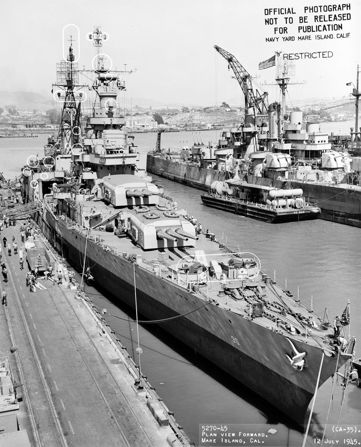 The US Navy Portland-class heavy cruiser USS Indianapolis (CA 35) in port at the Mare Island Navy Yard, in Northern California following its final overhaul. The ship was sunk on July 30, 1945 by an Imperial Japanese submarine in the Philippine Sea following delivery of parts for Little Boy, the first atomic bomb used in combat, to the United States air base at Tinian.